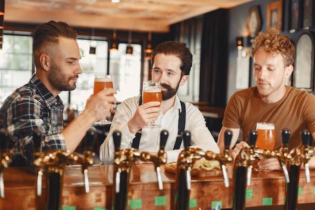 Spotkanie z najlepszymi przyjaciółmi. trzech szczęśliwych młodych mężczyzn w casual rozmawia i pije piwo siedząc razem w barze.