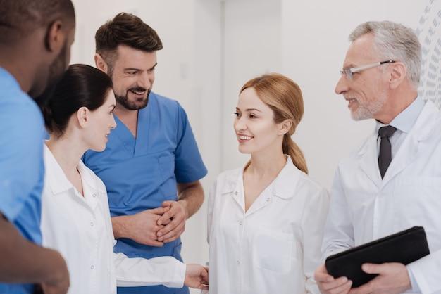Spotkanie z nowym młodym kolegą. życzliwi, pozytywni lekarze cieszący się godzinami pracy w klinice i pracujący w jednym zespole przy jednoczesnym wyrażaniu pozytywności i poznaniu nowego pracownika