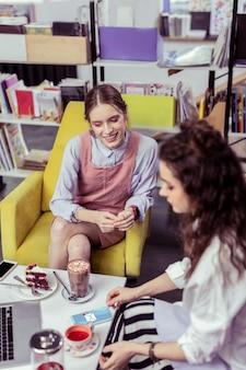Spotkanie z przyjacielem. uśmiechający się rozpromieniony dziewczyna ze skrzyżowanymi nogami szuka smartfona jej przyjaciółki, podczas gdy ona odbiera wiadomość