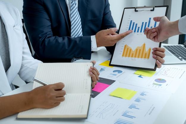 Spotkanie zespołu biznesmenów i biznesmenów w celu zaplanowania strategii zwiększania dochodów firmy. przeprowadź burzę mózgów, przeanalizuj wykresy i porozmawiaj o sukcesie nowego celu.