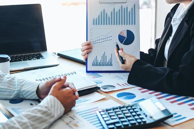 Spotkanie zespołu biznesowego planowanie strategii z nowym planem projektu startowego wykres finansów i gospodarki z udaną pracą zespołową na laptopie