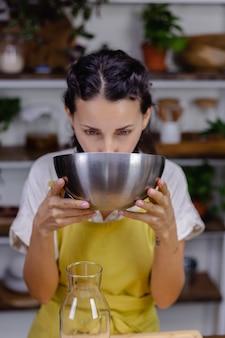 Spragniona kobieta pije mleko migdałowe z metalowej miski w kuchni