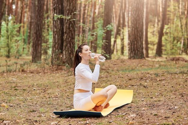 Spragniona kobieta ubiera stylową białą odzież sportową, siedząc na karemacie na ziemi i pijąc wodę z butelki, trenując na łonie natury, ćwicząc w lesie.