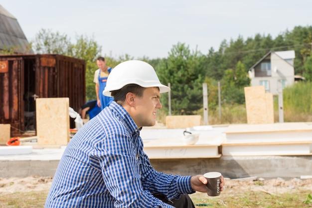 Spragniony budowniczy robi sobie przerwę na kawę siedząc widok z boku z kubkiem kawy w dłoniach, podczas gdy jego ekipa kontynuuje pracę na budynku za nim
