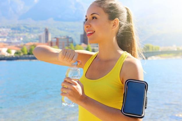 Spragniony fitness kobieta otwiera butelkę wody po treningu na świeżym powietrzu. dopasuj kobietę za pomocą aplikacji fitness na smartfonie na opasce jako monitora aktywności.