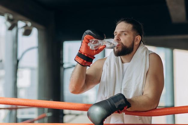 Spragniony męski bokser bierze przerwę pije z butelki z wodą po treningu w gym.