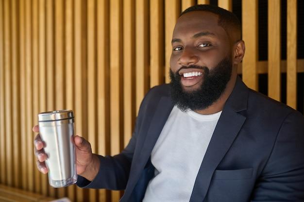 Spragniony. mężczyzna w garniturze trzymający butelkę i wodę pitną