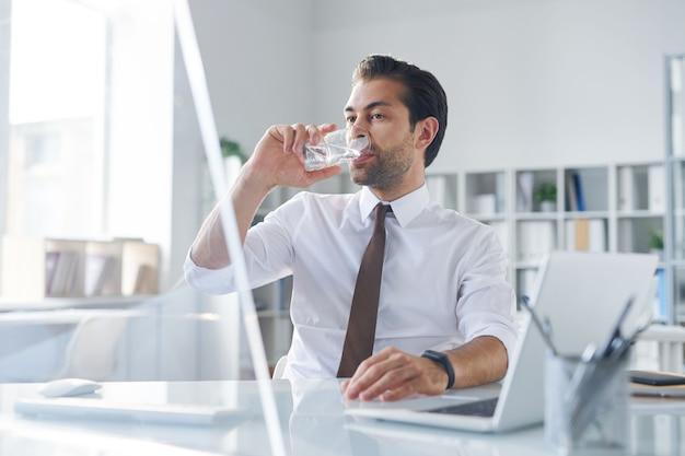 Spragniony młody pośrednik o szklance wody siedząc przed monitorem komputera w biurze