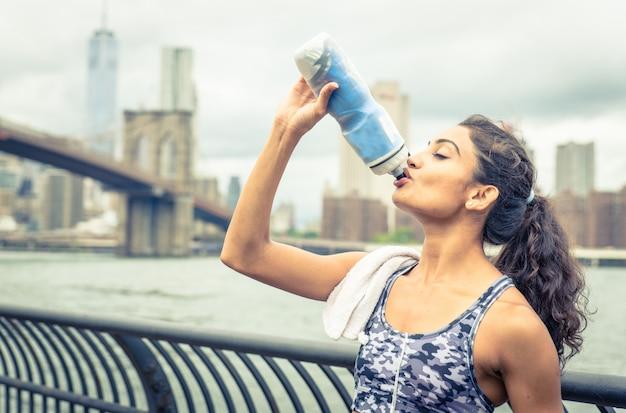 Spragniony sportowiec pije po długim pobycie w nowym jorku. most brookliński i linia horyzontu w tle