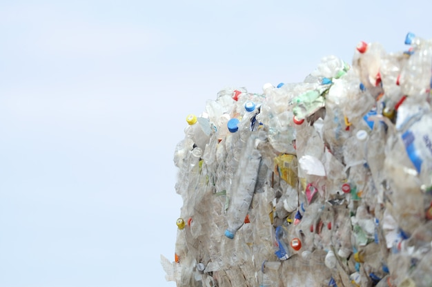 Sprasowane bele plastikowych butelek gotowe do recyklingu na tle błękitnego nieba