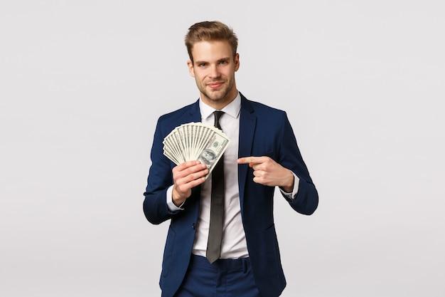 Sprawdź, jak wygląda sukces. przystojny biznesmen z gotówką w rękach, wskazujący pieniądze i uśmiechnięty pewnie, przechwalający się, dyskutuje jak zarządzać biznesem, rozpoczynając własną firmę