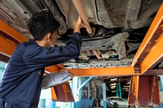 Sprawdź listę. mężczyzna mechanik naprawia silnik na podnośniku samochodowym. za pomocą narzędzi do naprawy samochodu w garażu. koncepcja samochodu serwisowego.