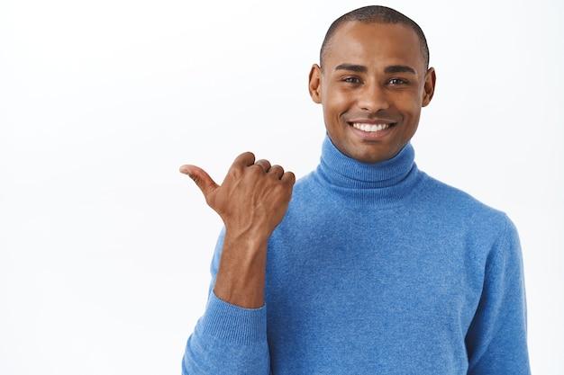 Sprawdź mój nowy samochód na zewnątrz. portret zadowolonego, dumnego, uśmiechniętego afroamerykańskiego mężczyzny wskazującego kciuk w lewo i uśmiechającego się usatysfakcjonowanego