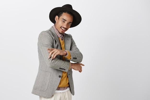 Sprawdź mój nowy strój. portret stylowego, pewnego siebie ciemnoskórego ucznia w modnym kapeluszu, wykonującego fajne gesty, tańczącego lub pozującego do pokazu ubrań, uśmiechającego się