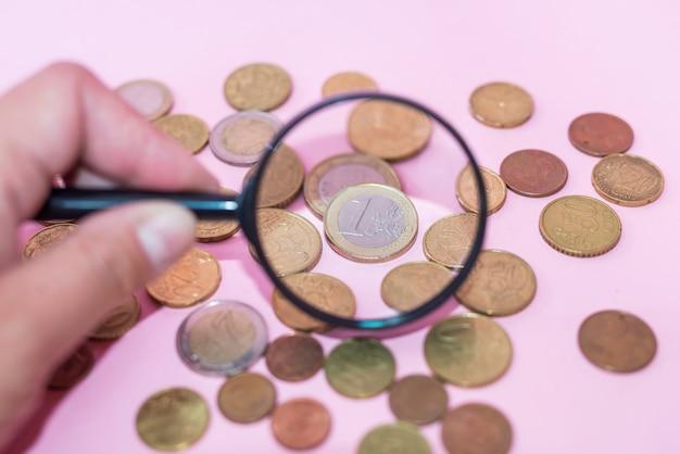 Sprawdź monety z lupą na różowym tle. monety euro przez szkło powiększające.