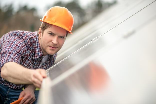Sprawdź poziom. młody dorosły mężczyzna w kasku budowlanym, patrząc z bliska na powierzchnię budynku z tabletem w ręku