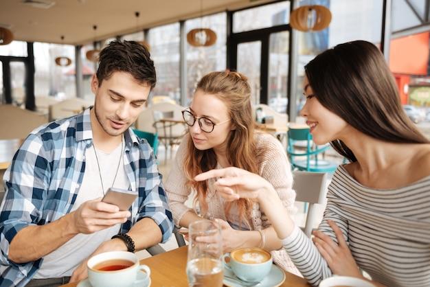 Sprawdź to. ładna młoda azjatka wskazuje na swoich przyjaciół, którzy używają smartfona w kafeterii.