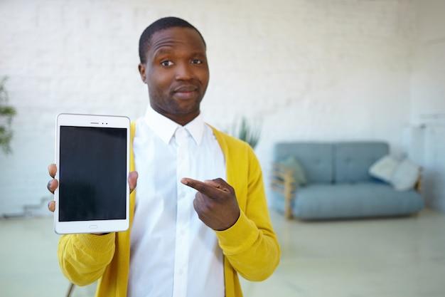 Sprawdź to. obraz pewnego siebie, nieogolonego, młodego afroamerykańskiego faceta pozującego w pomieszczeniu i wskazującego palcem wskazującym na nowoczesne, zupełnie nowe urządzenie elektroniczne z ekranem dotykowym z pustą przestrzenią do kopiowania.