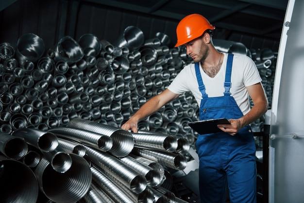 Sprawdza jakość materiału. mężczyzna w mundurze pracuje nad produkcją. nowoczesna technologia przemysłowa.