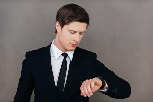 Sprawdzam czas. pewny siebie młody mężczyzna w formalnej odzieży, patrząc na swój zegarek, stojąc na szarym tle
