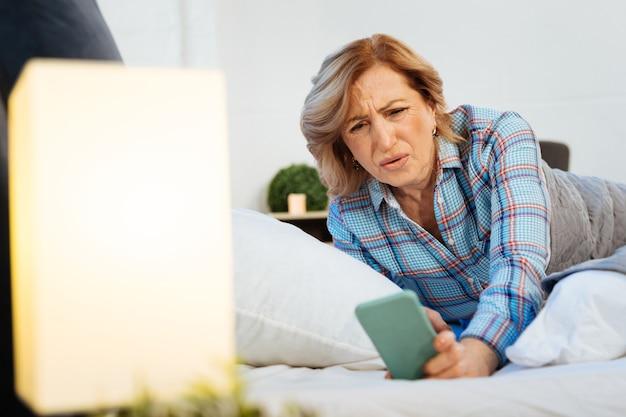 Sprawdzam czas. zdezorientowana, krótkowłosa dorosła kobieta w jasnej piżamie patrząca na ekran swojego smartfona z nieprzyjemnym spojrzeniem