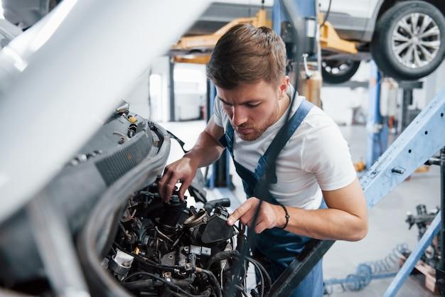 Sprawdzam czy wszystko jest podłączone poprawnie. pracownik w niebieskim mundurze pracuje w salonie samochodowym.