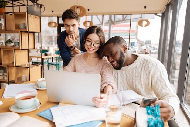 Sprawdzam nowy projekt. trzech kolegów razem korzysta z laptopa podczas pracy nad projektem w kawiarni.