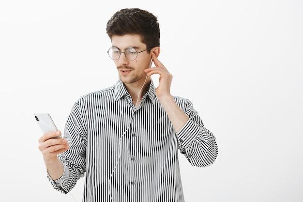Sprawdzam świetny utwór ulubionej piosenkarki. portret skupionego przystojnego, zdumionego mężczyzny z wąsami, trzymającego smartfon, wybierającego piosenkę podczas słuchania muzyki w słuchawkach na szarej ścianie