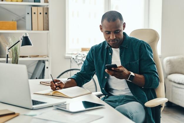 Sprawdzam wiadomości. rozważny młody afrykanin w koszuli za pomocą smartfona siedząc w biurze