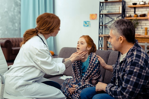 Sprawdzam wszystko. miły profesjonalny lekarz dotykający szyi pacjenta podczas badania lekarskiego