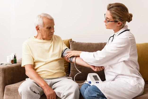 Sprawdzanie ciśnienia krwi. młoda kobieta lekarz i starszy mężczyzna.