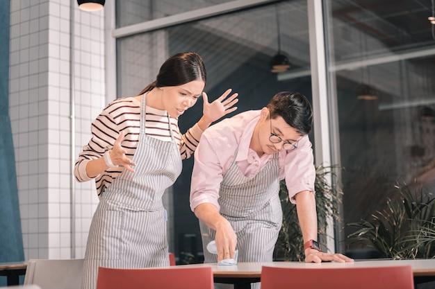 Sprawdzanie czystości. właściciel małej kafeterii czuje się niezadowolony z kontroli czystości stołu