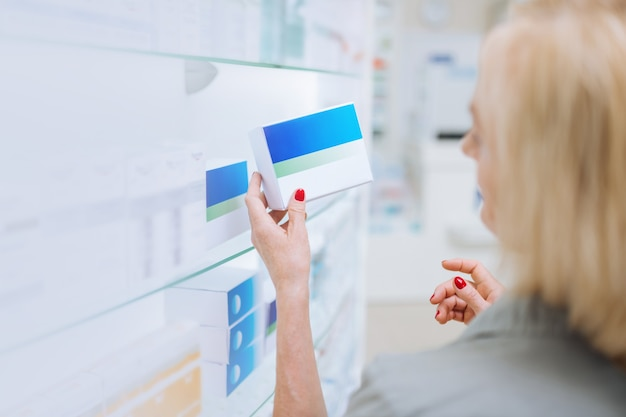 Sprawdzanie informacji. uważny blond klient podnoszący rękę podczas czytania informacji na pudełku