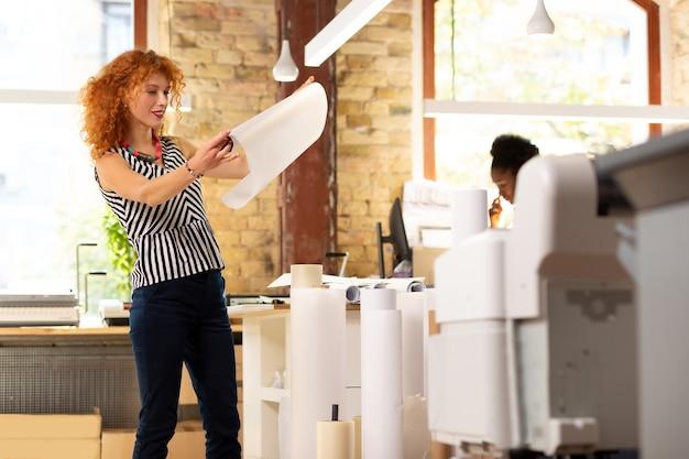Sprawdzanie jakości. rudowłosa stylowa pracownica biura wydawniczego sprawdzająca jakość papieru