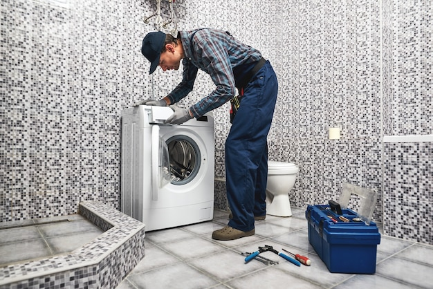 Sprawdzanie pracy pralki pracujący człowiek hydraulik w łazience