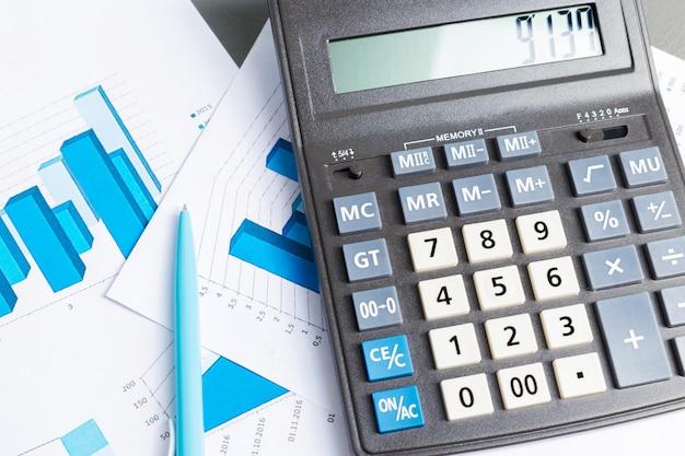 Sprawdzanie raportu księgowego na stole biznesowym. kalkulator