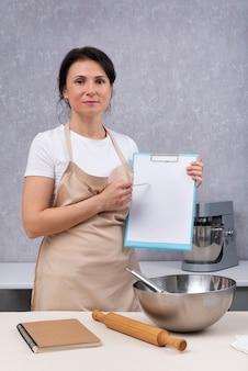 Sprawdzanie standardów sanitarnych w kuchniach restauracyjnych. kobieta w kuchni trzyma dokumenty w dłoniach. rama pionowa.