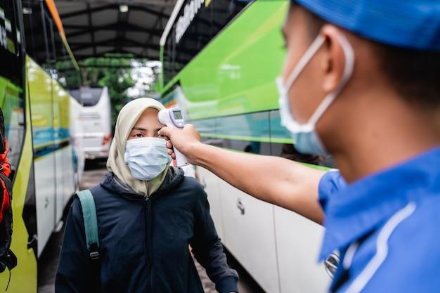 Sprawdzanie temperatury pasażera z azji za pomocą termoguna przed jazdą autobusem