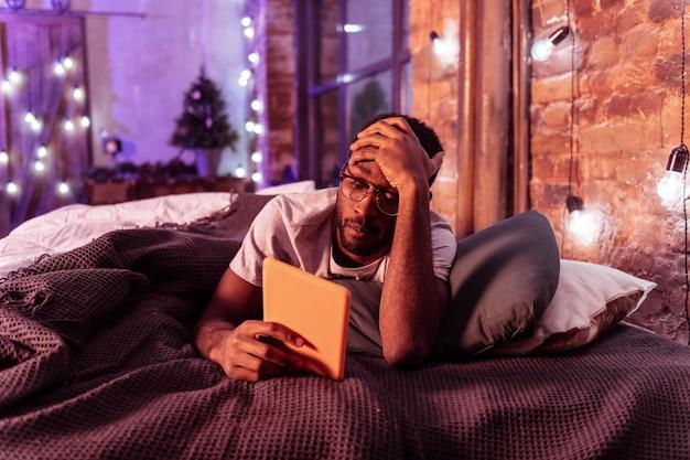 Sprawdzanie treści. zmęczony ciemnoskóry mężczyzna z czarnym zarostem podpierającym głowę podczas czytania z tabletu przed snem