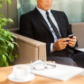 Sprawdzanie wiadomości biznesowych. pewny siebie dojrzały mężczyzna w formalwear pisanie wiadomości na swoim telefonie komórkowym i siedząc na krześle na zewnątrz z filiżanką kawy na pierwszym planie