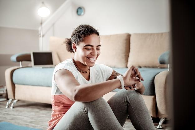 Sprawdzanie wskaźników. radosna młoda dama śmiejąca się i patrząca na ekran swojego zegarka po intensywnym treningu