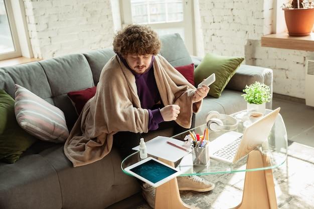 Sprawdzanie wykresów. mężczyzna pracujący w domu podczas kwarantanny koronawirusa lub covid-19, koncepcja zdalnego biura. młody biznesmen, kierownik wykonujący zadania ze smartfona, laptopa, tabletu ma konferencję online.