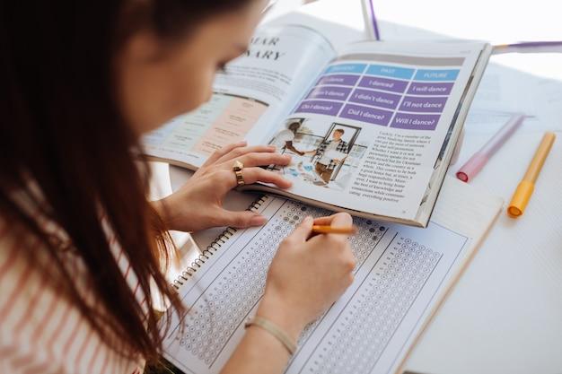 Sprawdzenie testowe. skoncentrowana brunetka pochyla głowę podczas robienia notatek