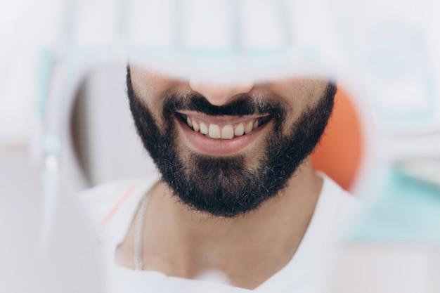 Sprawdzić. lustro w dłoni ładnie wyglądającego mężczyzny z doskonałym uśmiechem, którego używa do sprawdzenia ostatecznego wyglądu swojego uśmiechu