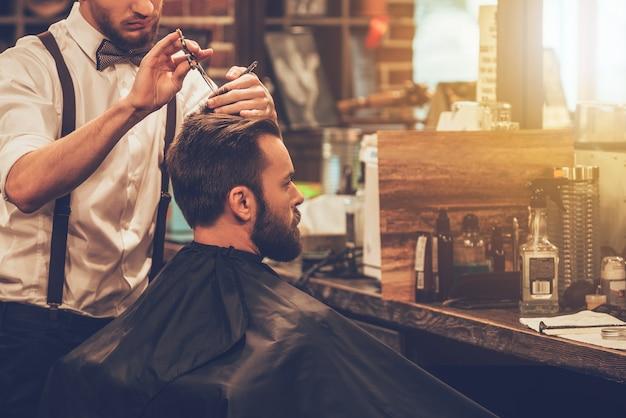 Sprawia, że włosy wyglądają magicznie. młody brodaty mężczyzna ostrzyżony przez fryzjera siedząc na krześle u fryzjera