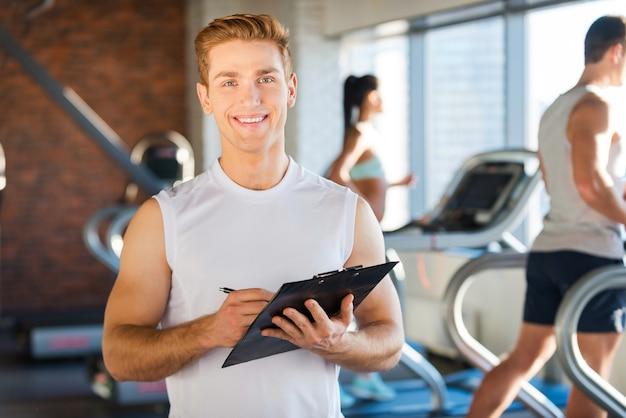 Sprawię, że będziesz zdrowy! przystojny młody mężczyzna trzyma schowek i uśmiecha się, podczas gdy w tle ludzie biegają na bieżni