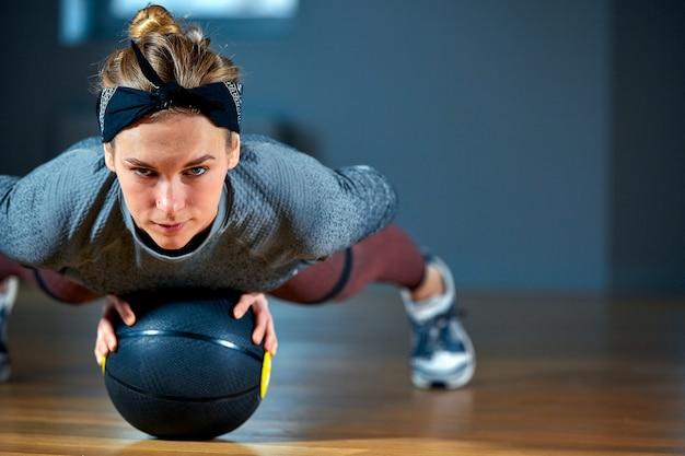 Sprawna i muskularna kobieta o przenikliwych oczach robi intensywny trening rdzenia z kettlebell w siłowni. kobieta ćwiczy przy crossfit gym.