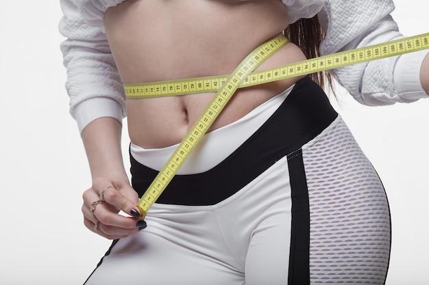 Sprawna i zdrowa młoda dama mierząca talię przy pomocy centymetra i milimetra. na białym tle obraz na białym tle.