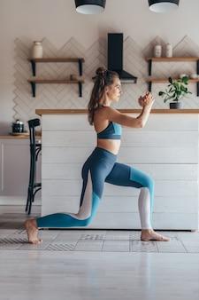 Sprawna kobieta ćwiczeń w domu robi lunges ćwiczenia.
