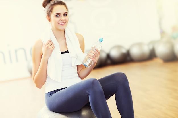 Sprawna kobieta siedzi na piłce w siłowni